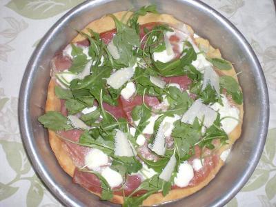 Pizza con prosciutto crudo, rucola e scaglie di parmigiano